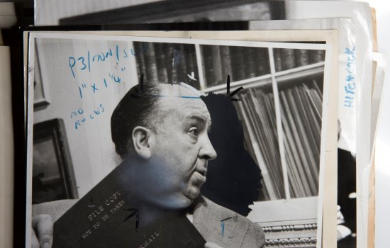 A folder of archive photographs, the first one is an image of Alfred Hitchcock