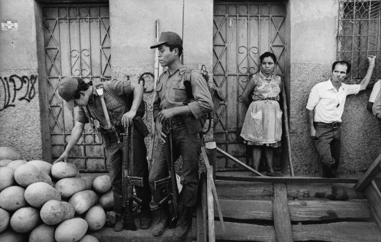 Soldiers examine watermelons at a street stall on the outskirts of San Miguel, March 1984 © Mike Goldwater