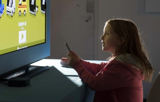 A girl playing a videogame on a large screen at Yorkshire Games Festival