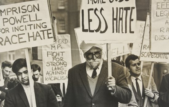 Image shows a protest march with placards including 'Imprison Powell for inciting race hate' and 'More houses, more jobs, less hate'