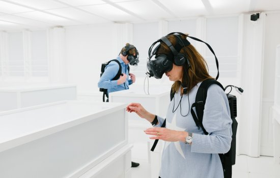 Image shows two people wearing VR headsets exploring a plain white room