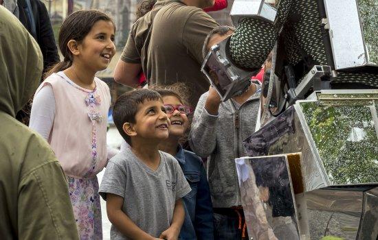 Children watching an outdoor theatre performance in Bradford