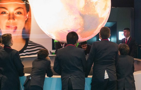 A group of students observing the Science on a Sphere display in Wonderlab