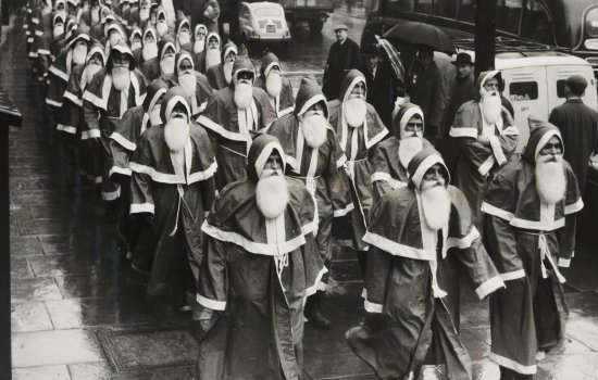 Black and white photograph of a large group of men dressed as Father Christmas
