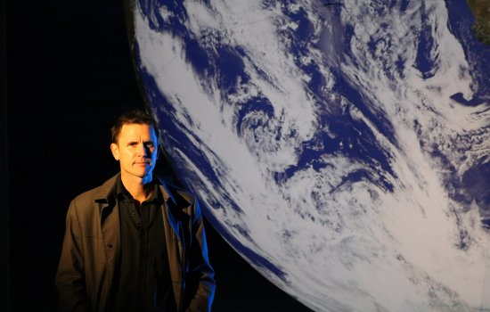 The artist Luke Jerram stands next to his artwork Gaia, an illuminated sculpture of Earth