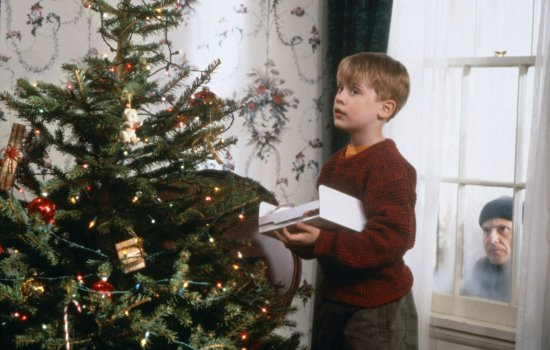 A boy decorating a Christmas tree while a man looks through a window at him