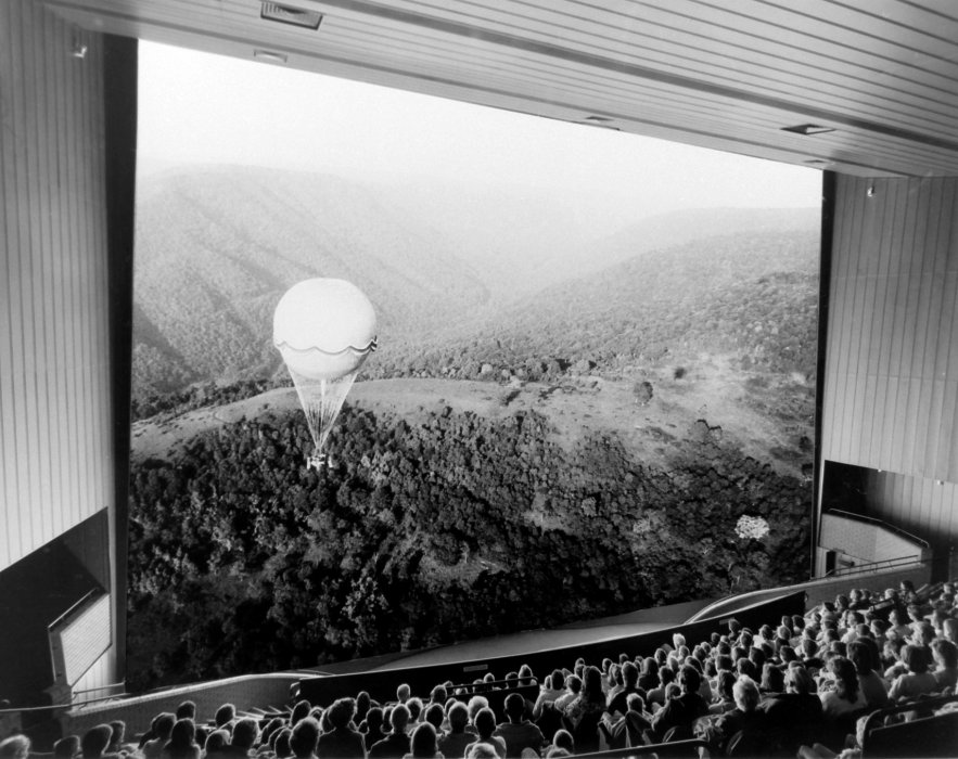 A black and white photograph of an audience looking at an IMAX cinema screen