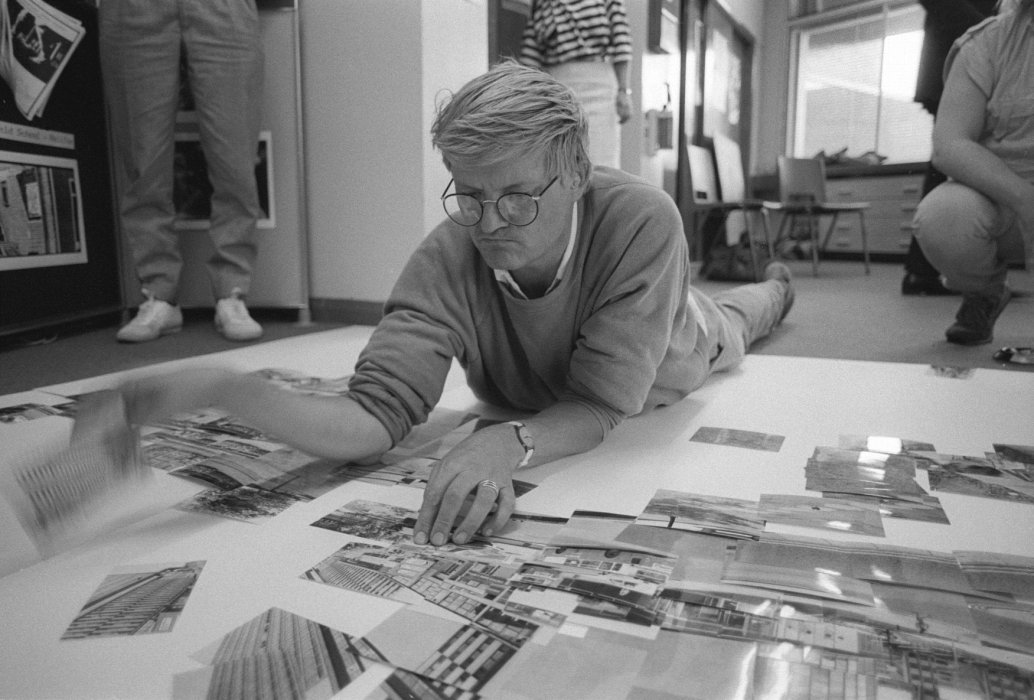 A black and white photography of David Hockney lying on the floor looking at images