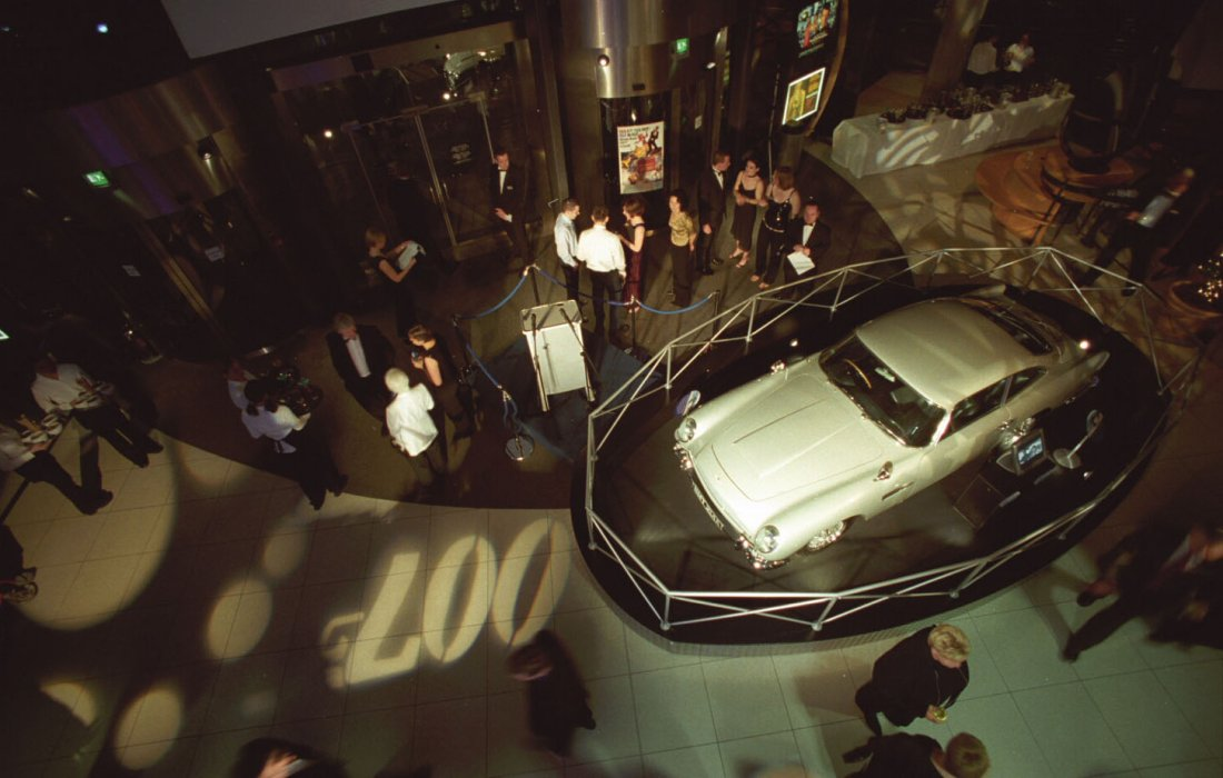 A birds-eye photograph of a silver car and the 007 logo