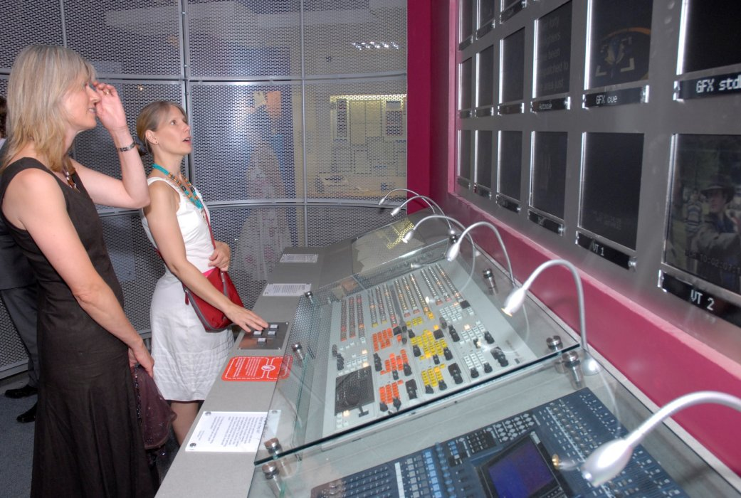 A photograph of two women looking at a mixing desk exhibit in a museum