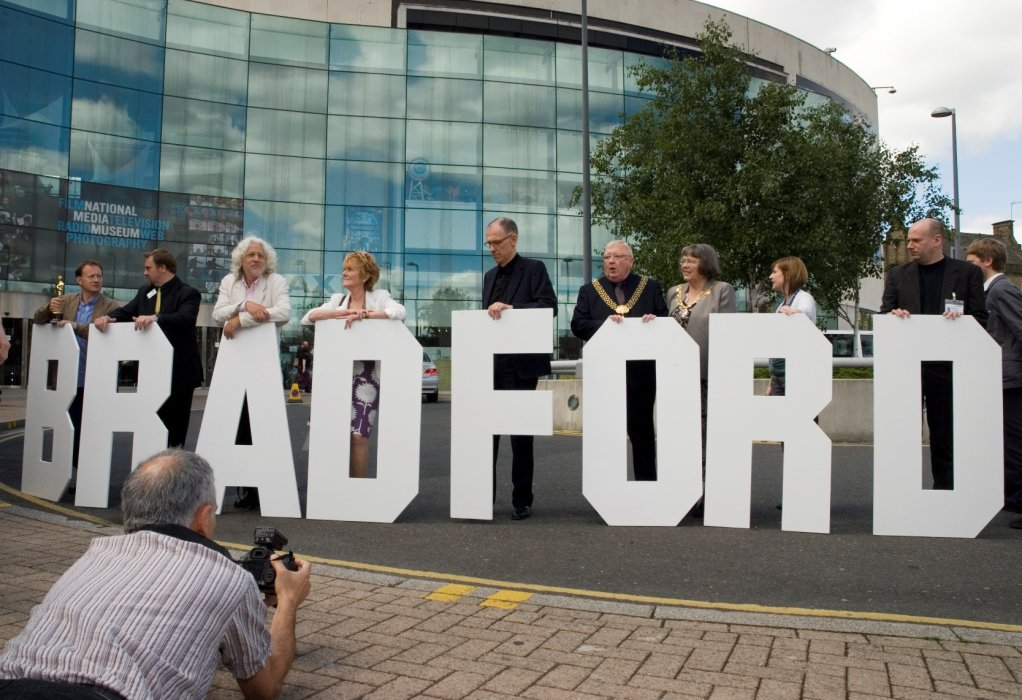 A group of people standing behind large letters spelling Bradford, in front of the Museum