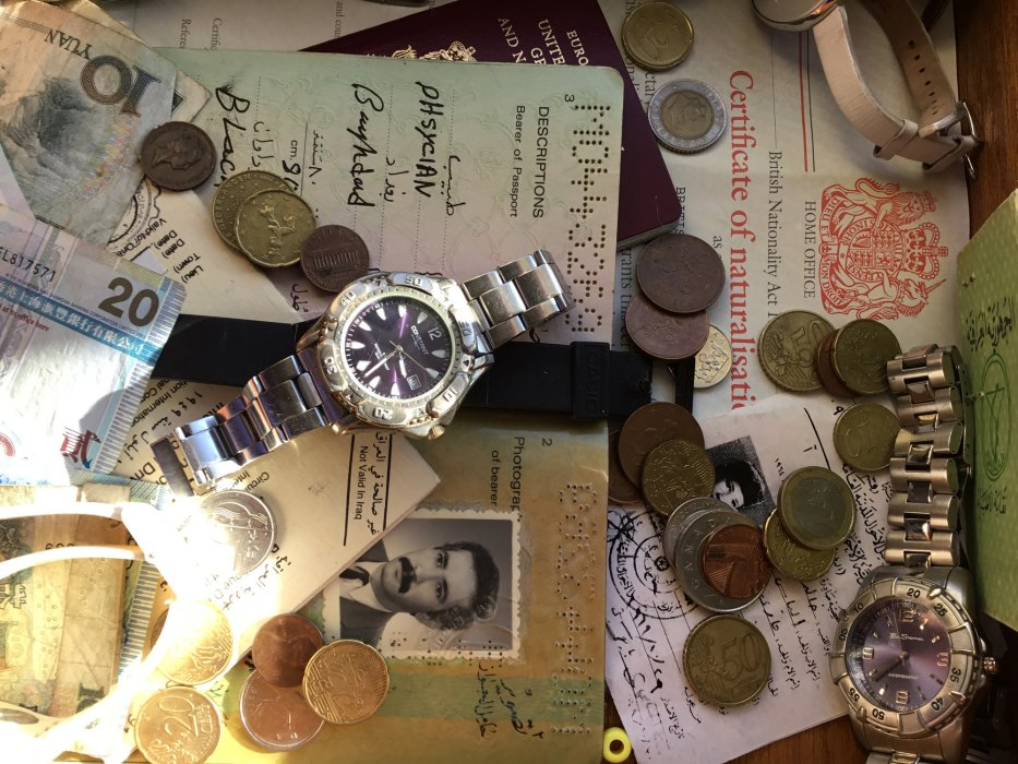 An image of watches, money and documents in a drawer