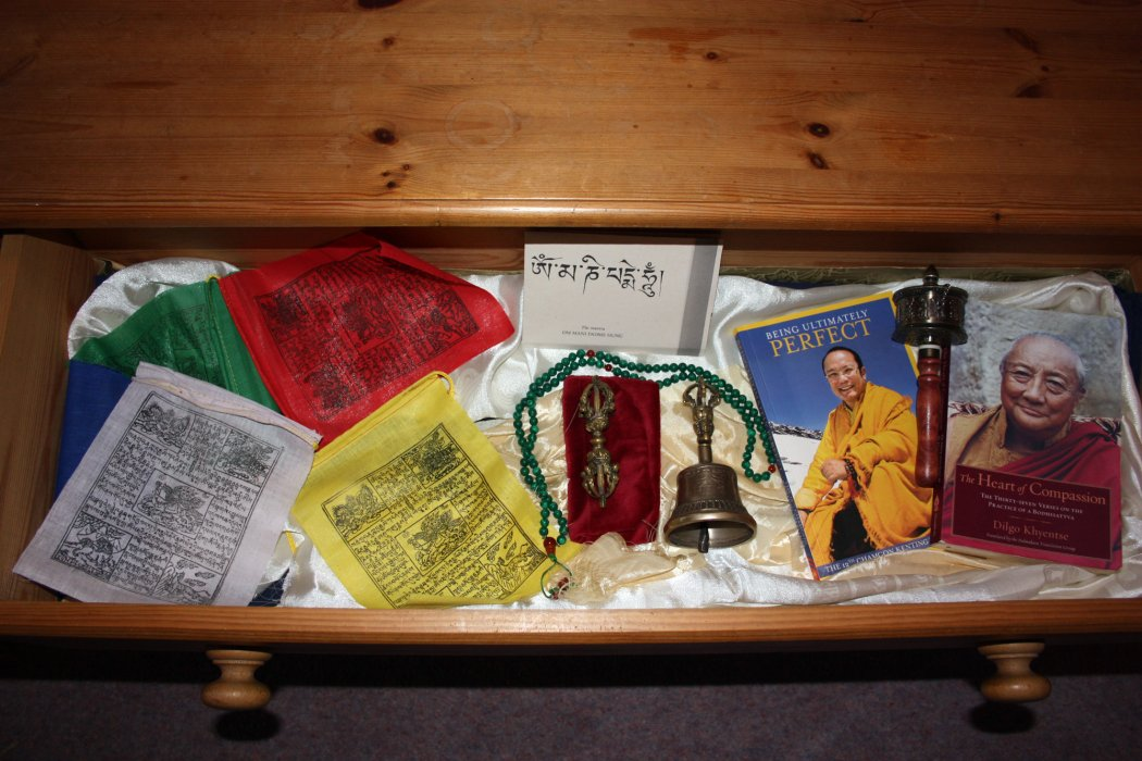 Image of Buddhist books and paraphernalia in a wooden drawer