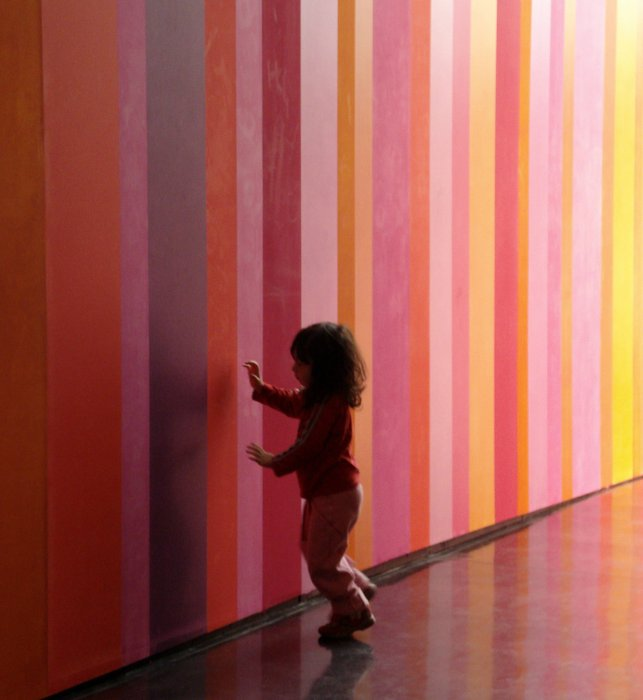 A child touching a multicoloured striped wall