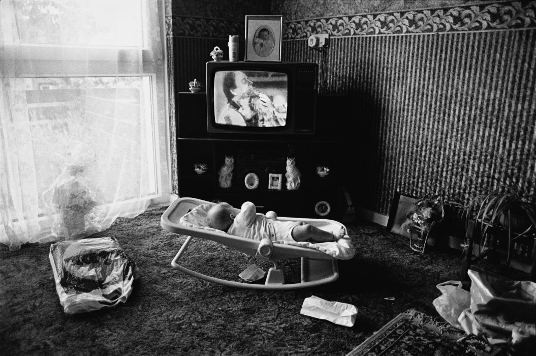 Baby and babysitter – the television, 'Neighbours', Penrhys, South Wales, 1994, Nick Danziger © Nick Danziger/nbpictures