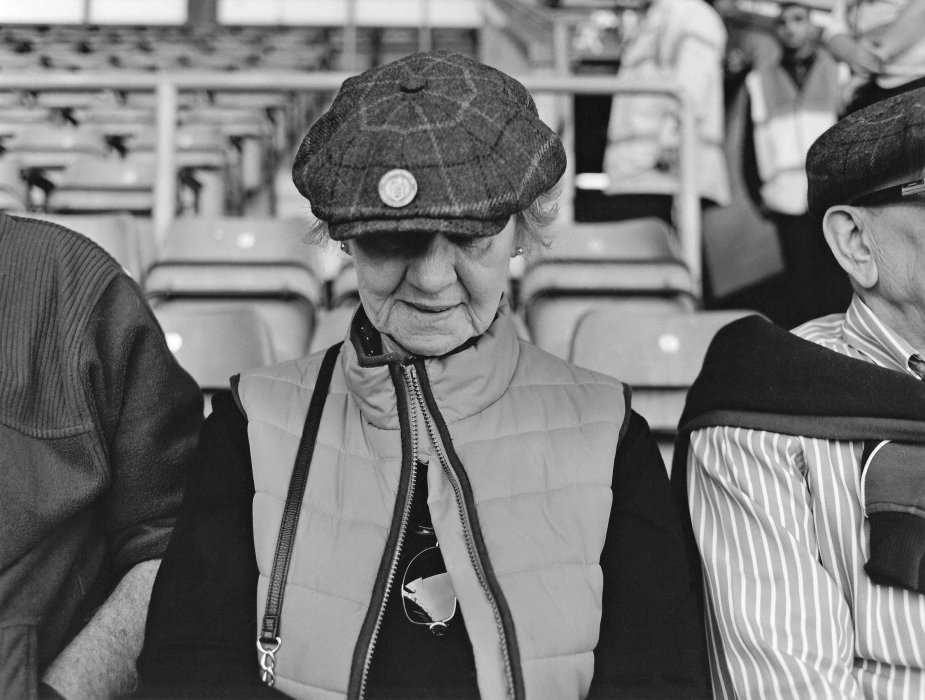Image shows a woman wearing a cap and gilet at a Bradford City match
