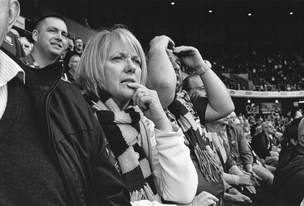 Image shows a woman looking pensive as she watches a Bradford City football match