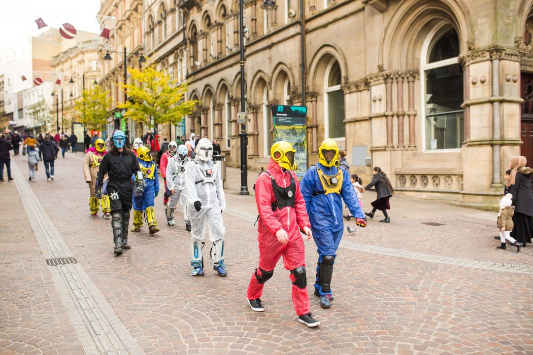Participants in The Displaced, wearing costumes, walk through Bradford