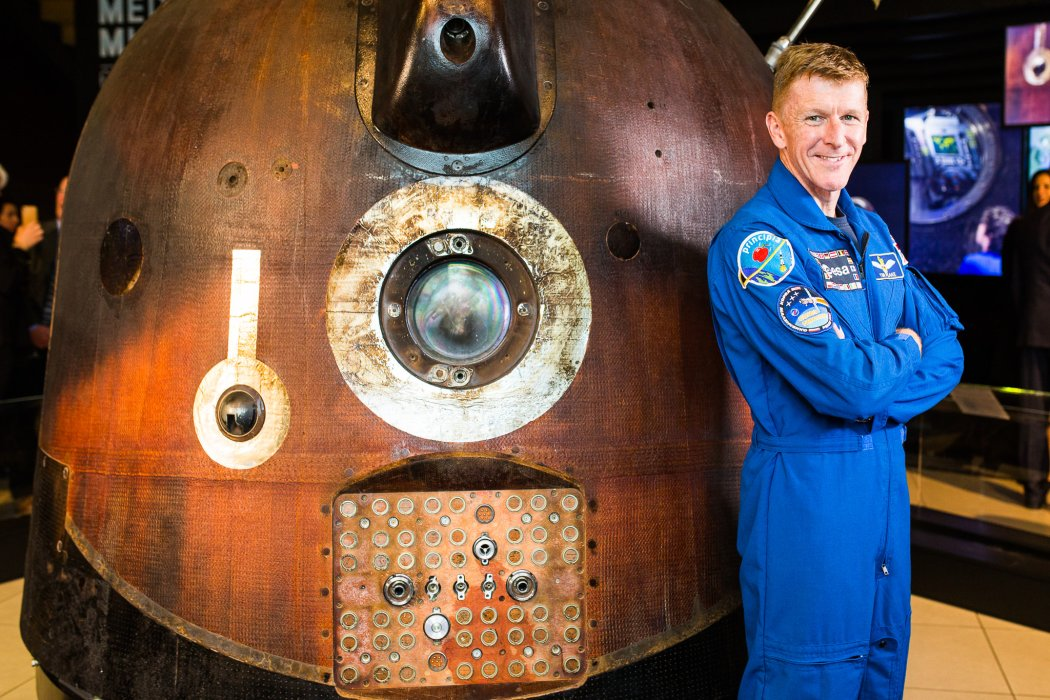 Tim Peake standing next to the Soyuz TMA-19M descent module
