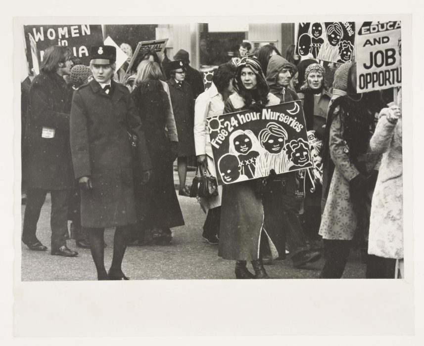 Black and white photograph of a group of women protesting, one carrying a sign reading 'Free 24 Hour Nurseries'