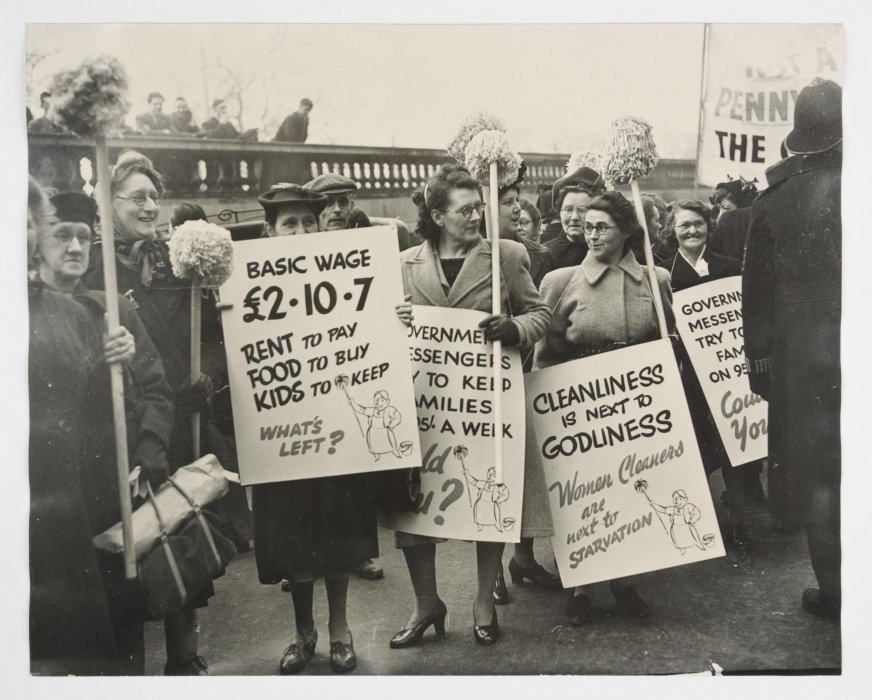 Black and white photograph of a group of women cleaners protesting; they are holding mops and placards. The front placard states their average wage (£2.10.7) and reads 'rent to pay, food to buy, kids to keep—what's left?'