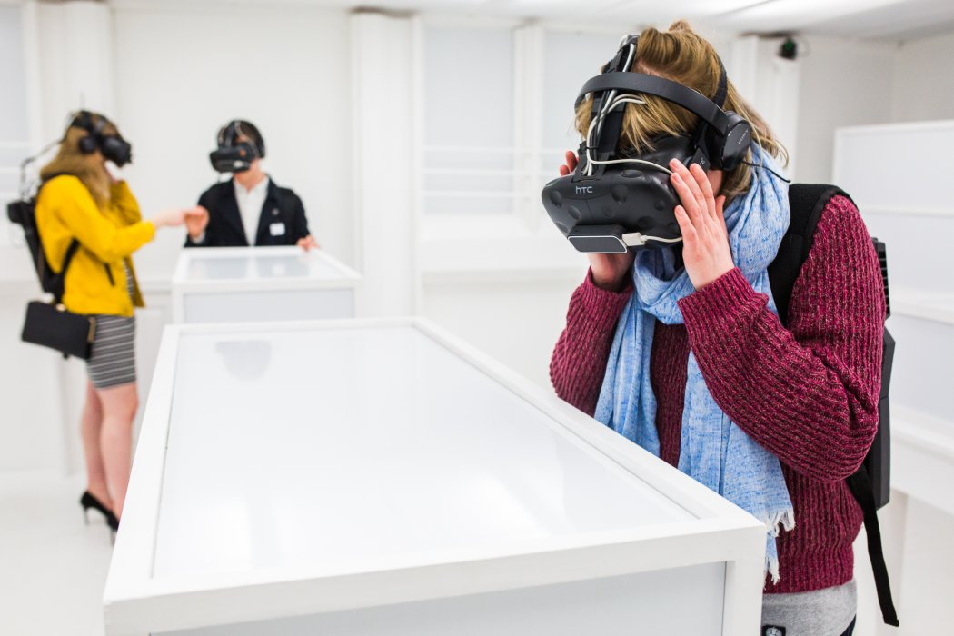 Visitors wearing VR headsets inside the Thresholds installation