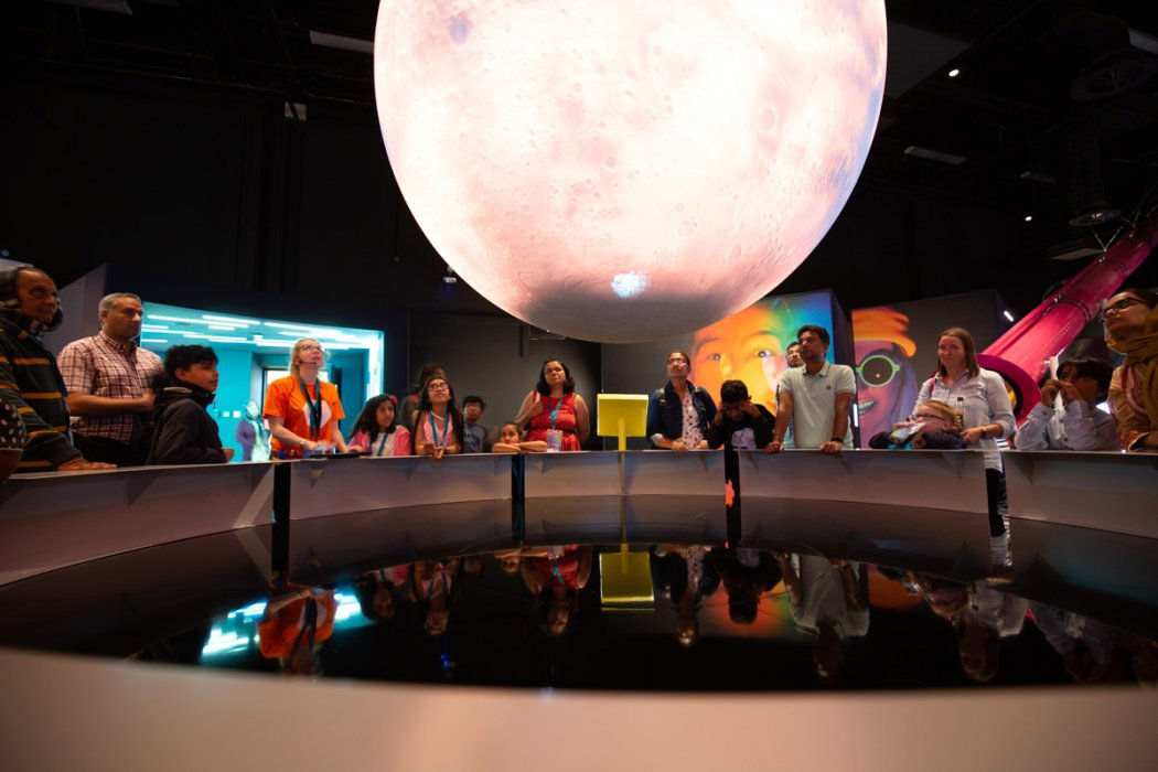 Visitors investigate the Science on a Sphere display in Wonderlab