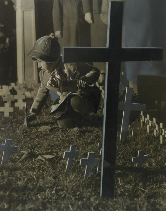 "A young girl placing a small cross in the ""Field of Remembrance"" at Westminster on Armistice Day, 1934"