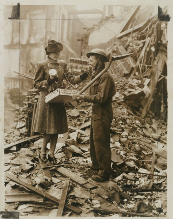 A woman selling a Remembrance Day poppy to a soldier amid the rubble of the Blitz