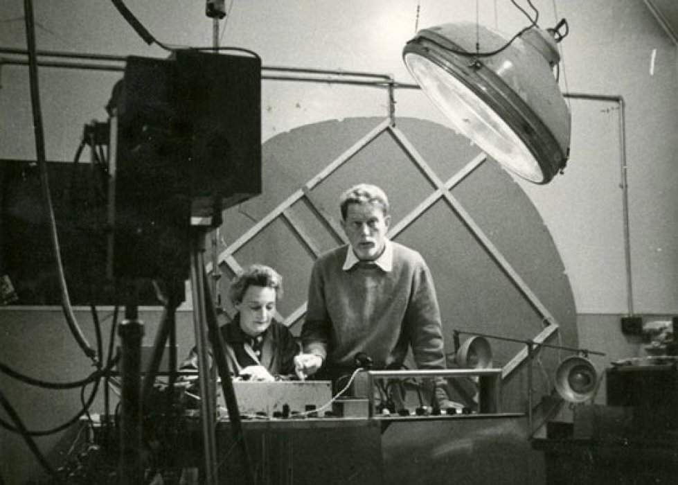 Black and white photograph of a man and a woman surrounded by scientific equipment