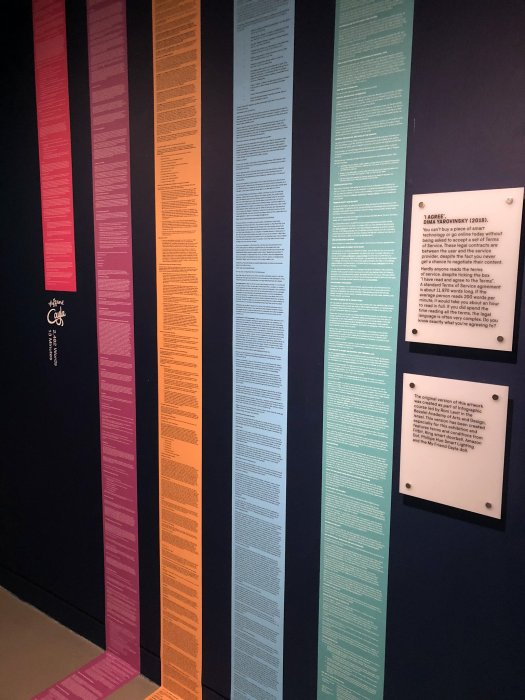 Image of the artwork I Agree showing colourful printouts of terms of service on a wall