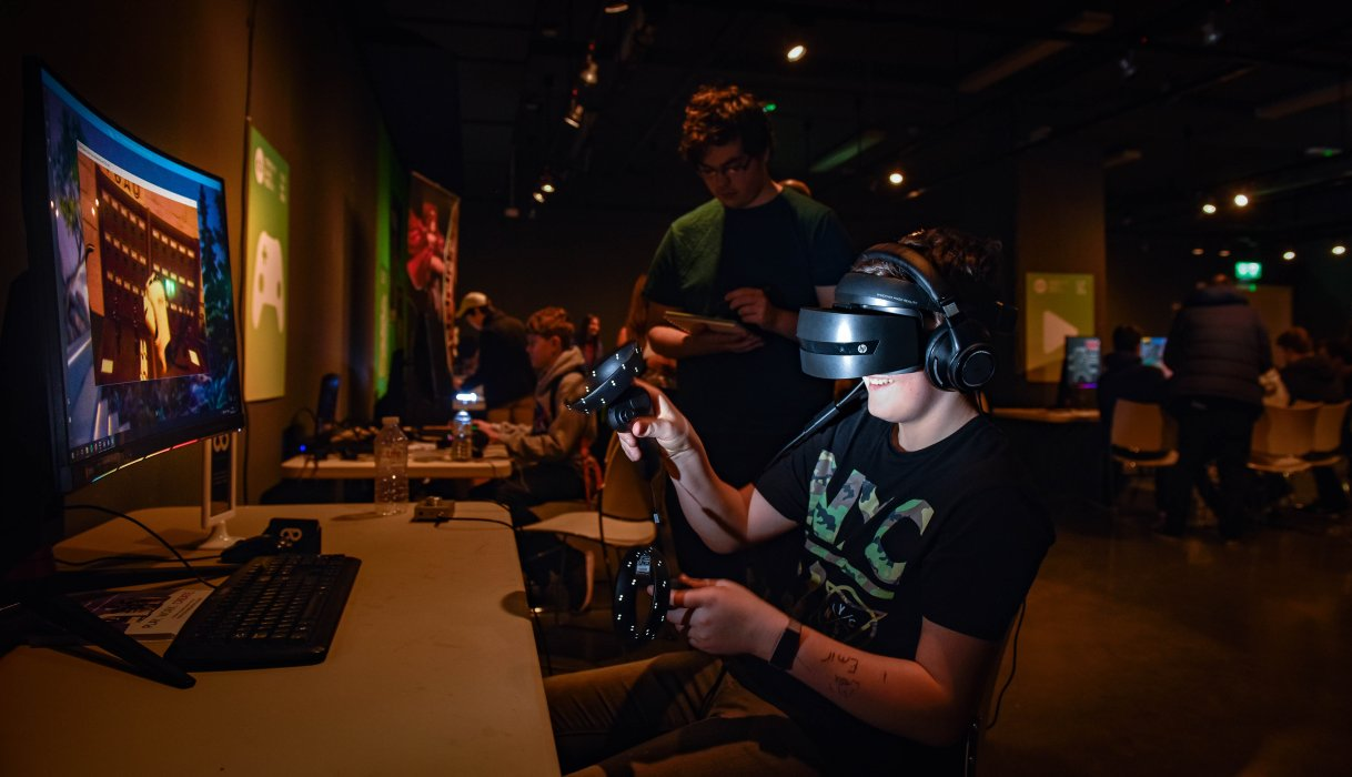 A visitor wearing a headset tests out a virtual reality game as part of the Northern Games Showcase