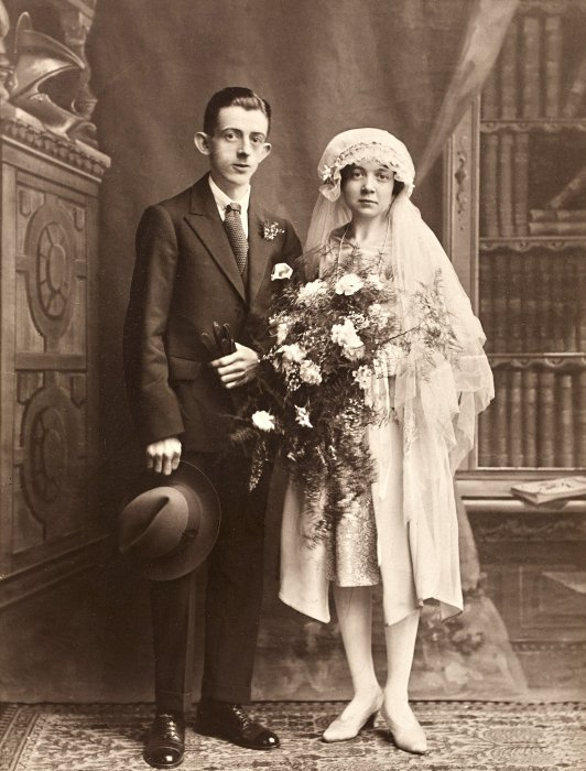 A young couple in wedding outfits, photographed at Belle Vue Studio