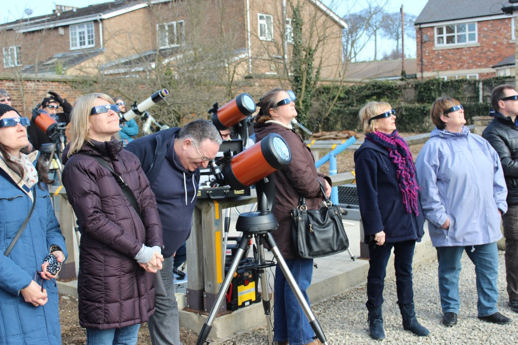 WYAS members wearing protective glasses watch a partial solar eclipse