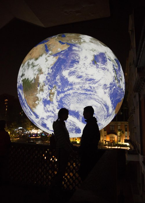 Two people, seen in silhouette, stand in front of Gaia, an illuminated sculpture of Earth, at Hsinchu New Year Festival in Taiwan