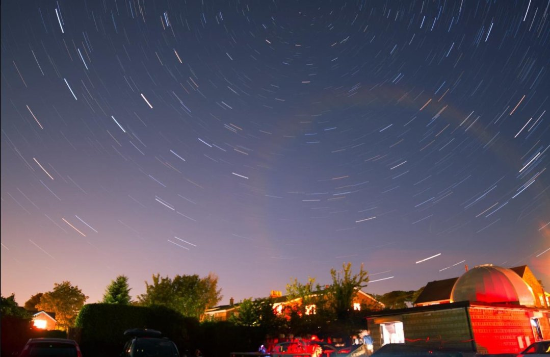 A long exposure photograph showing star trails above buildings