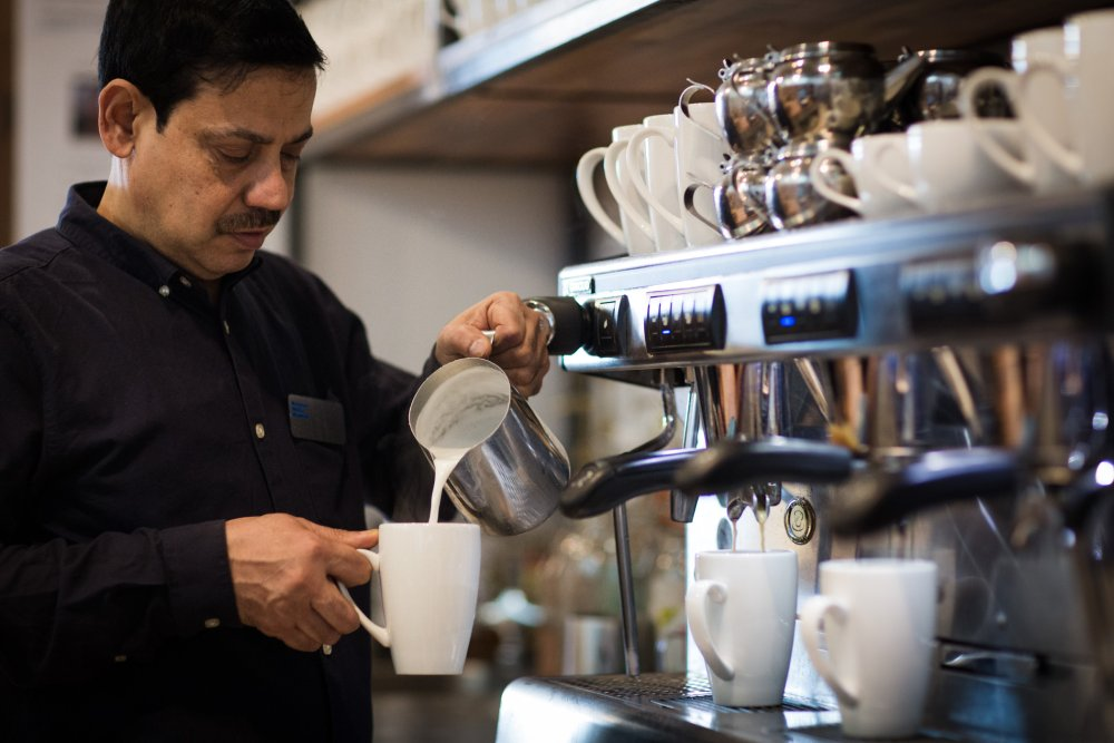 A barista pouring coffee in the Media Café