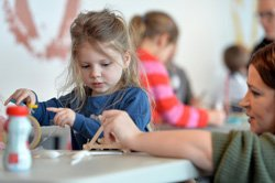 Image shows a family taking part in a creative activity in Makespace at the National Science and Media Museum