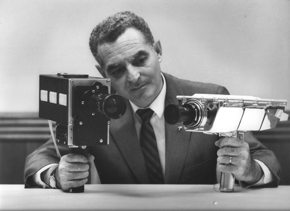 Stan Lebar, the project manager for Westinghouse's Apollo Television Cameras, shows the Field-Sequential Color Camera on the left, and the Monochrome Lunar Surface Camera on the right