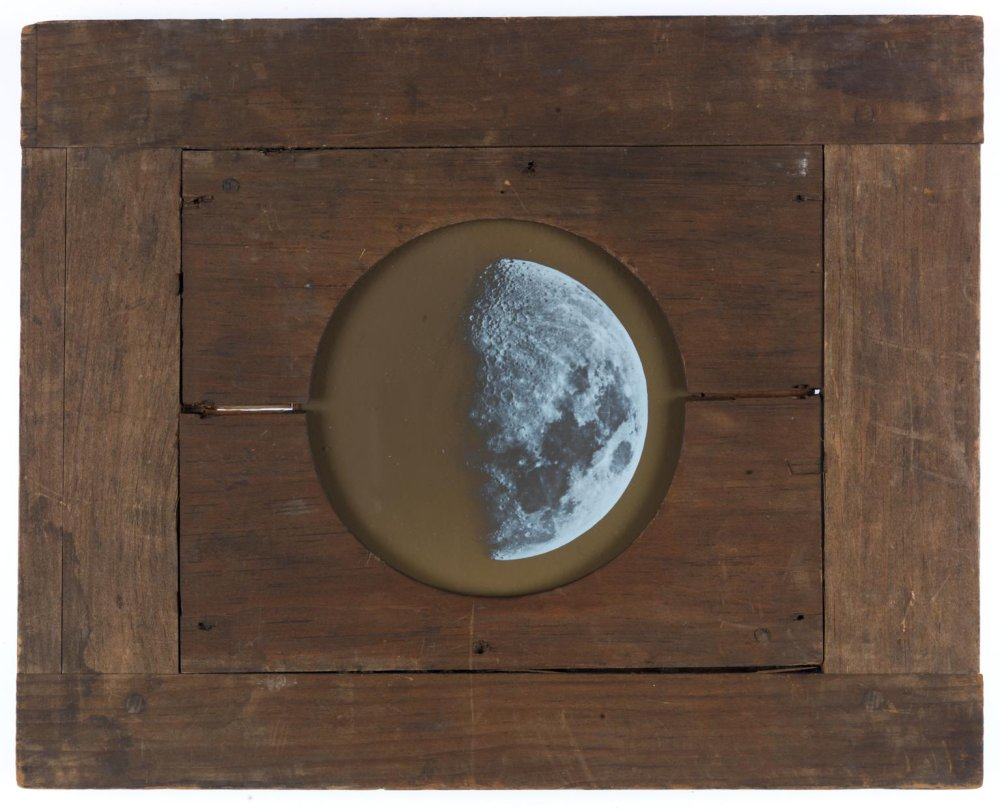 Magic lantern slide showing the Moon. A circular illustration of the Moon is shown at the centre of a wooden board