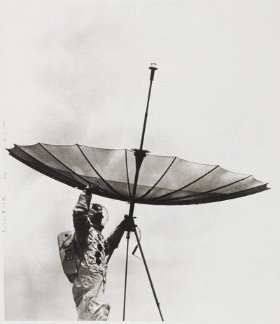 Black and white gelatin silver photograph entitled 'Moon Television Antenna'. Caption reads: RCA Engineer Bob Mason rehearses a scene Apollo 11 astronauts may enact on their visit to the moon by adjusting a fully-opened gold-plated wire mesh umbrella antenna to beam communication signals